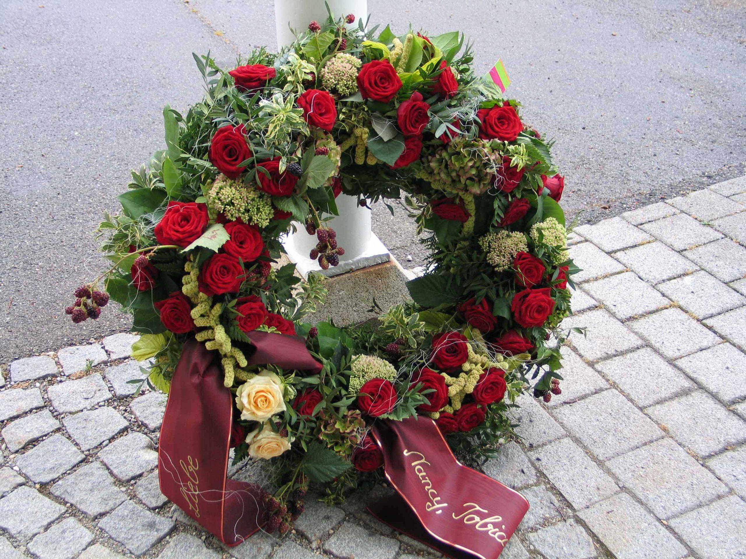 13 Rundgesteckter Trauerkranz mit roten Rosen